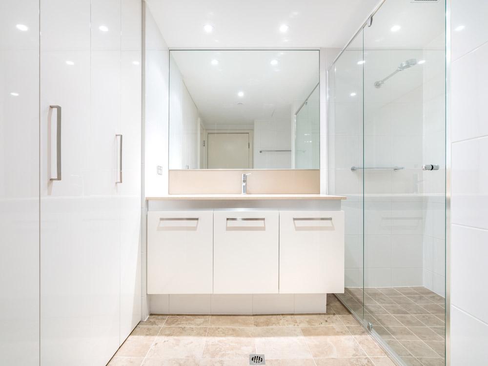 Helles Badezimmer mit weißer Spanndecke und Beleuchtung