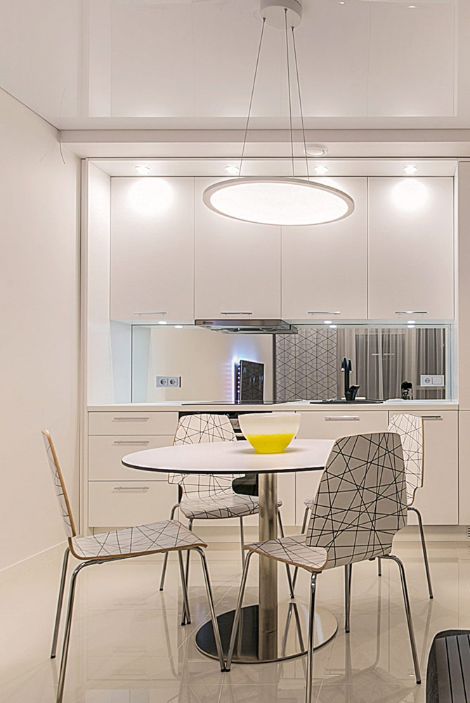 Küchenbereich mit Essstühlen und Hochglanz Spanndecke